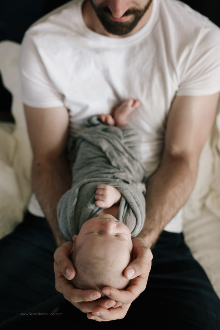 Dad holding his baby at newborn photography session