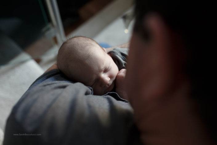 newborn baby in grandfather's arms