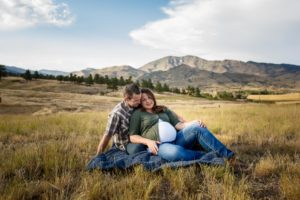 Johnston, Colorado maternity photographer, couple sitting in field